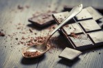 Cocoa Powder on spoon and Dark Chocolate background
