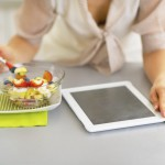Closeup on young woman with tablet pc eating fruit salad