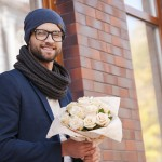 Waiting for her. Handsome young man in smart casual wear holding bouquet of flowers and smiling while standing at the street