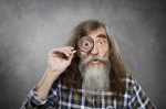 Senior old man looking through zoom magnifying glass. Funny elde