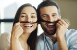 Playful couple. Beautiful young loving couple bonding to each other and smiling while making a fake mustaches from her hair