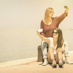 Hipster girlfriends taking a double selfie at wharf docks - Conc