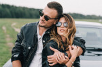 stylish-couple-in-sunglasses-embracing-near-luxury-car-in-4541585