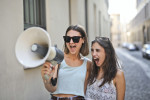 cheerful-young-women-screaming-into-loudspeaker-3764551