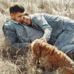 happy-couple-with-dog-lying-on-dry-grass-4005079