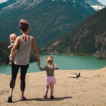 mother-and-children-walks-near-body-of-water-1157399