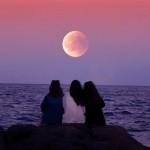three-women-sitting-on-rock-infront-of-ocean-3348489