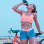 woman-drinking-water-while-standing-beside-her-bike-1302925