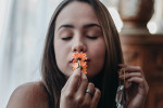 portrait-of-woman-kissing-orange-flowers-3115637